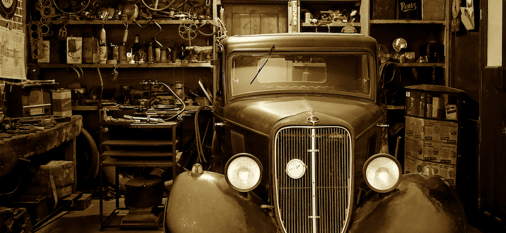 An antique Ford sits abandoned in an unused in an old garage, filled with automotive paraphernalia.