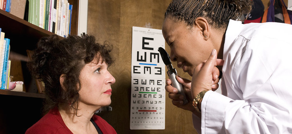 A woman being given an eye exam by her doctor.