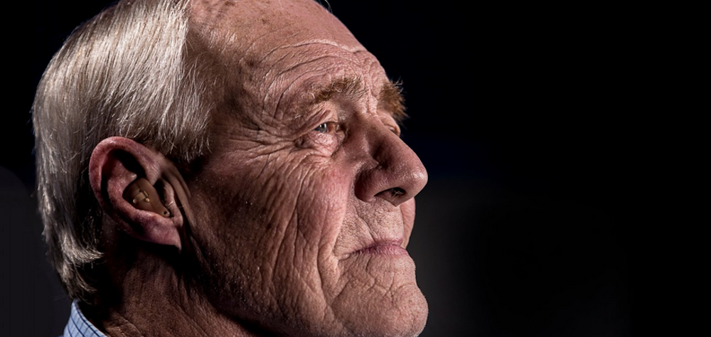 Close up profile of an elderly man with hearing aids, who looks off to the distance.
