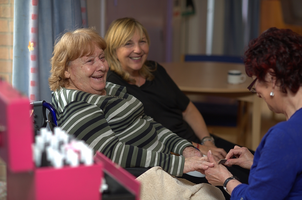 A smiling older woman in a wheelchair enjoys a manicure with her younger female companion at her side.