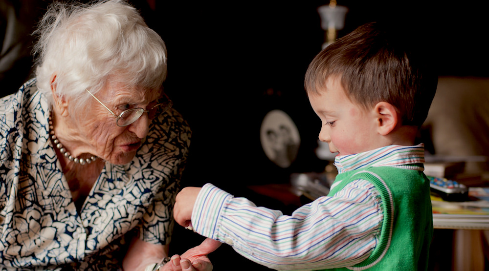 A very young boy shows a toy to his elderly grandmother.