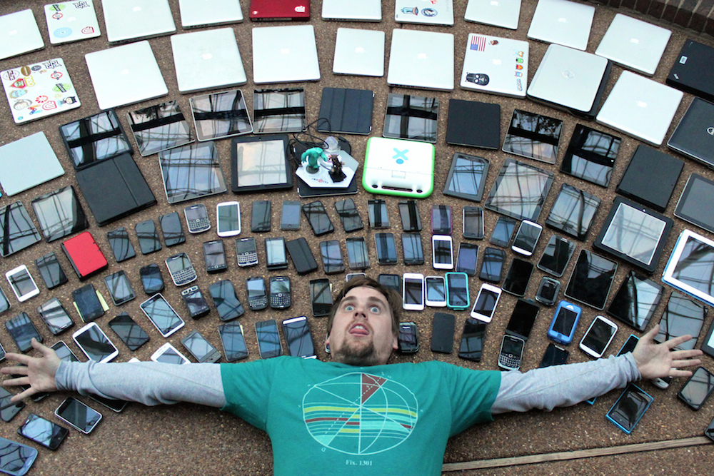 A young man looks overwhelmed by the array of technology available to him.