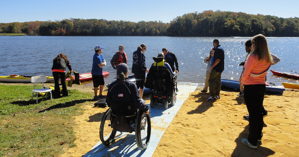 Group of people in wheelchairs approach a lakeside ramp as they prepare to board kayaks.