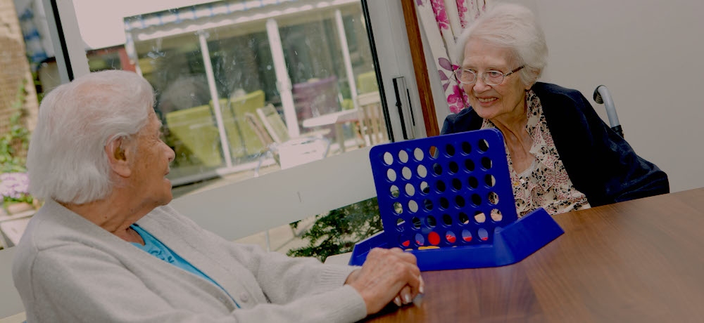 Two older women, one with a hearing aid and the other in a wheelchair, play Connect Four.