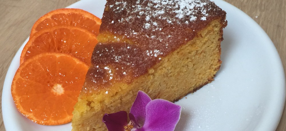 Piece of clementine and almond cake garnished with sliced clementine and a decorative flower