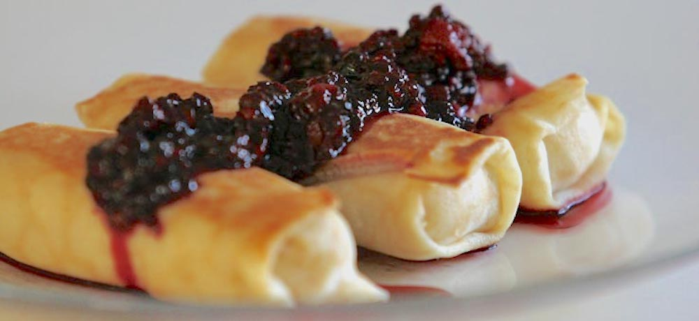 Cheese blintzes topped with fresh blackberries.