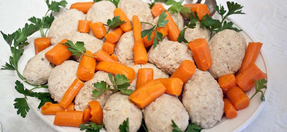 Freshly made gefilte fish chilled, along with horseradish of your choice and a sprinkling of the chilled carrots.