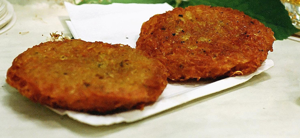 Two potato pancakes sit side by side on a plate.