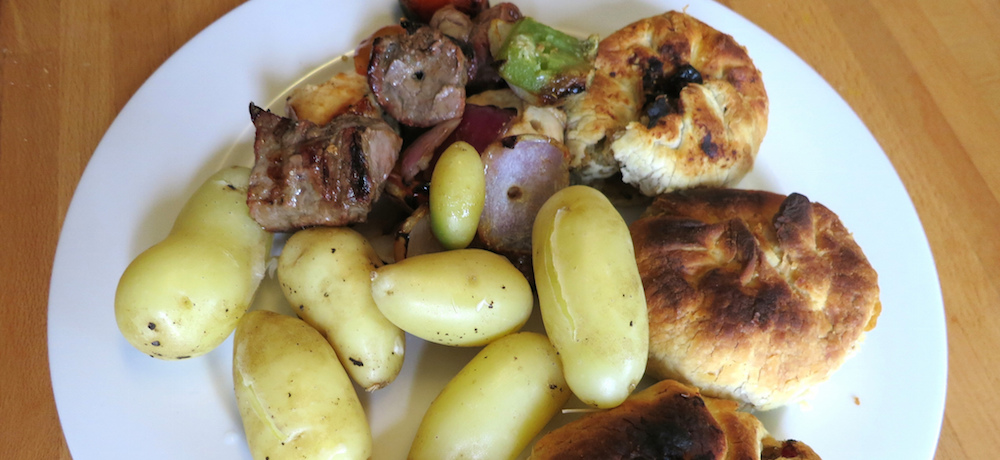 A plate of homegrown new potatoes, knishes and kebabs.