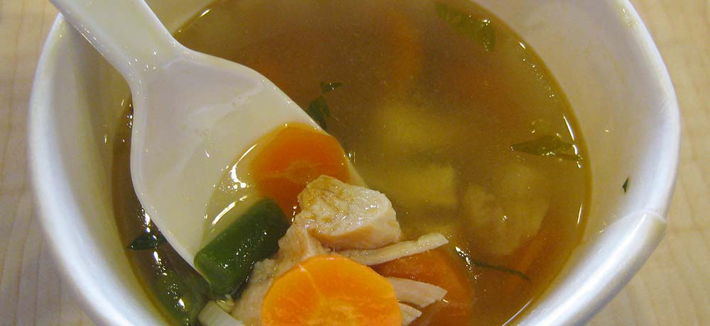 Chicken pieces and vegetables in chicken broth soup.
