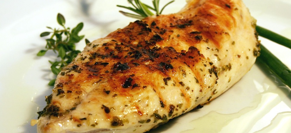 Roast chicken breast is placed on a plate and garnished with fresh herbs.