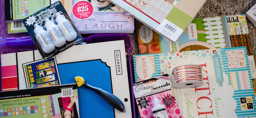 A collection of scrapbooking items, including paper, glue, and custom cutting tools, fills a table. (Photo: Flickr.)