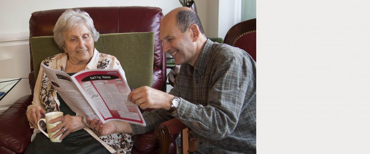 Man smiles while he is reading to his cheered mother.