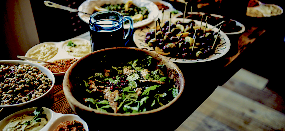 A wooden table is laden with vegan finger foods, dips, salads and spread.