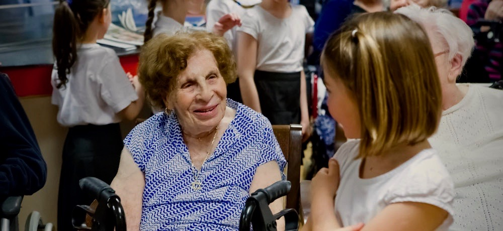 An older woman in a wheelchair smiles as she chats with a young girl.