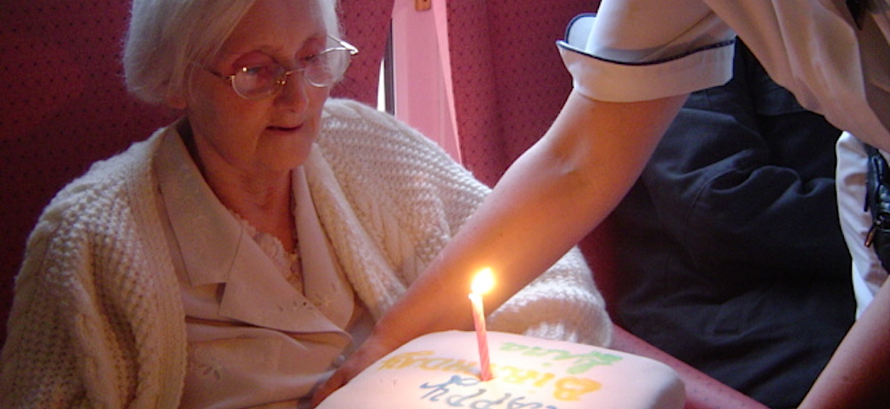 A homecare worker brings a birthday cake to woman.
