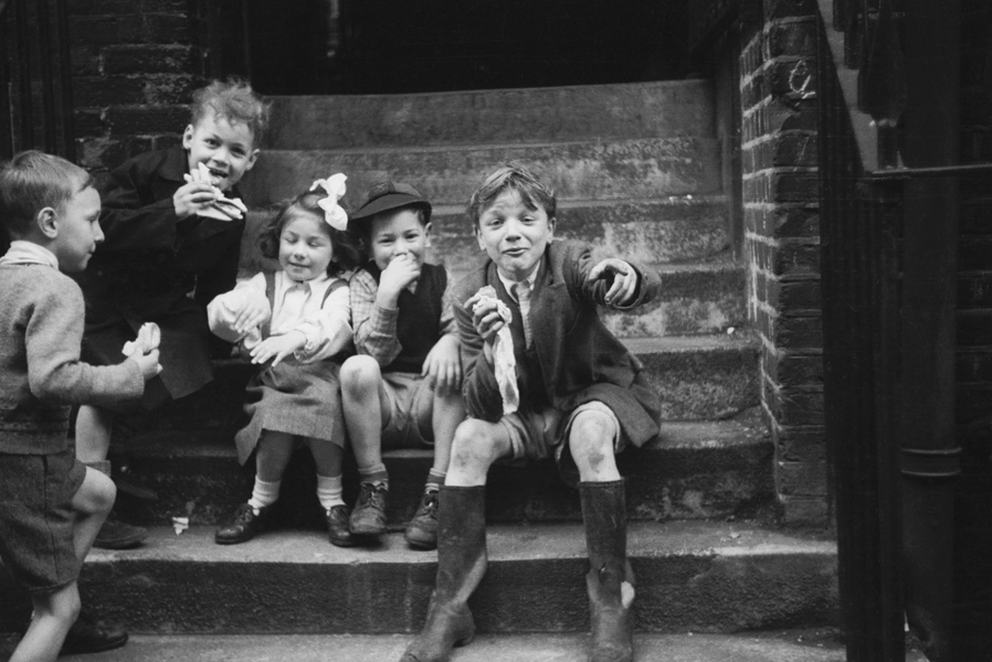 One girl and four boys from London's East End sit and laugh as they eat sandwiches.