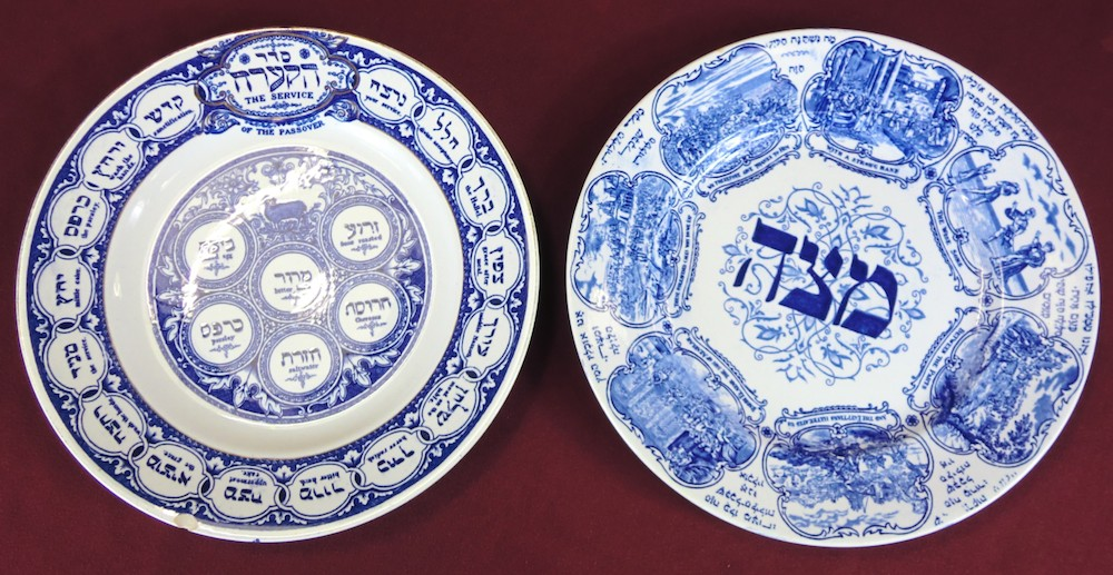 Two white Passover plates with blue artwork and embellishment.