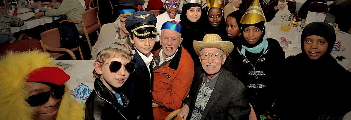 A crowd of children and older people wear costumes and smiles during a Purim party.