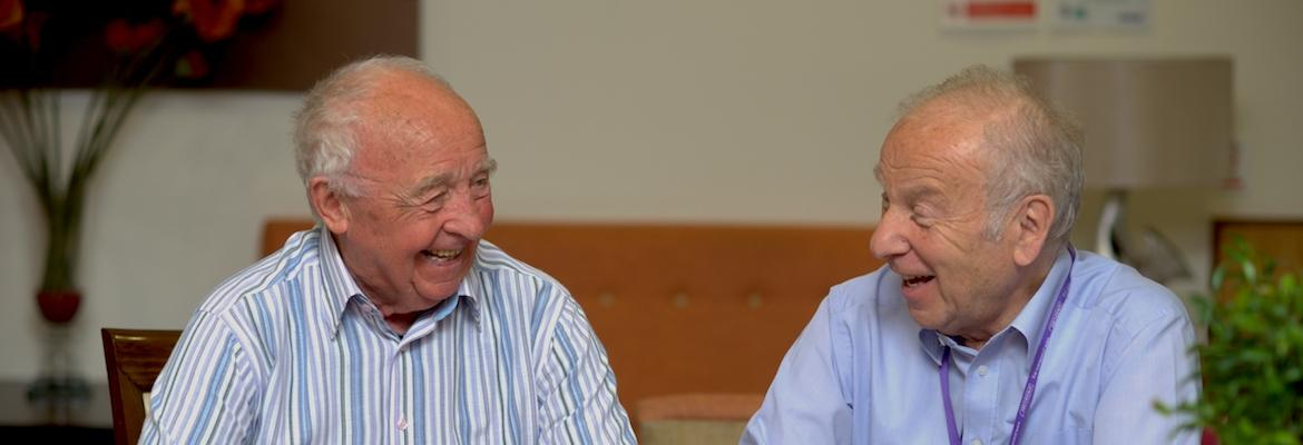 Two gentlemen laugh and chat as they sit together.