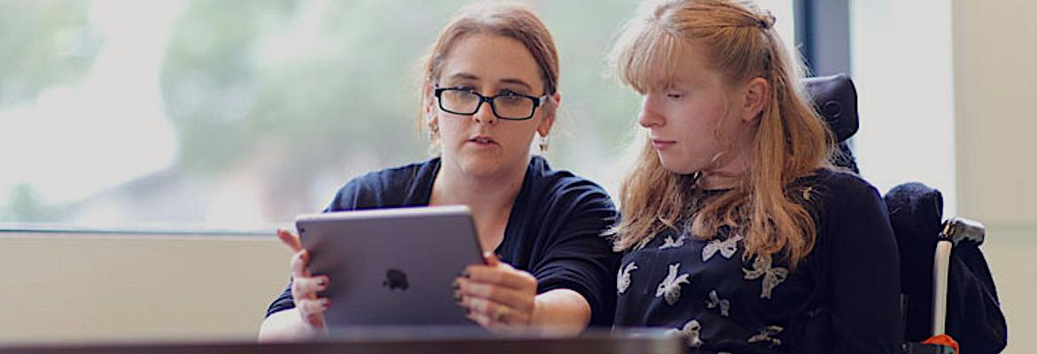 A woman on the left uses an app on an iPad with a college student in a wheelchair. This 'Voice It' app was an entry in the 2015 Summer of Student Innovation.