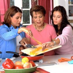 Three adult females in the kitchen preparing healthy food.