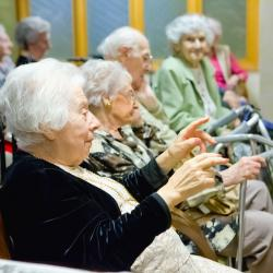 Older men and women with walking frames sit in a row; one woman in the foreground is particularly engaged and raises her hand as a gesture.