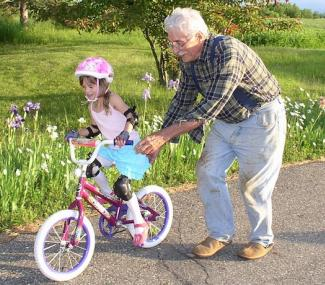 Young girl on a bike is wearing a helmet and being pushed by older man.