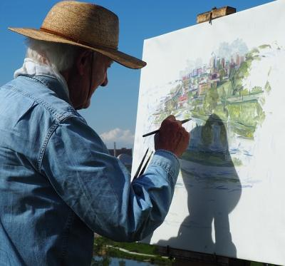 An older man wearing a sun hat is outside painting a canvas.
