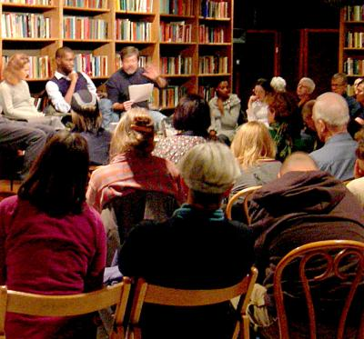 A reading is given by an author to a room full of people during a meeting of a local book club.