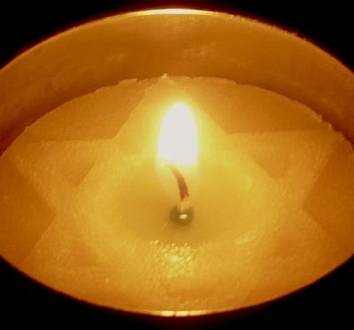 A special yellow candle is lit in a dark room on Yom Hashoah.