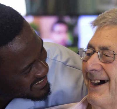 Carer and service user smile at each other.