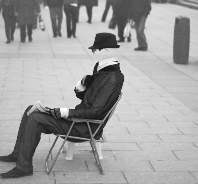 An invisible man dressed in a suit and wearing a hat and sunglasses sits on the pavement in a folding chair and is ignored by those who pass by.