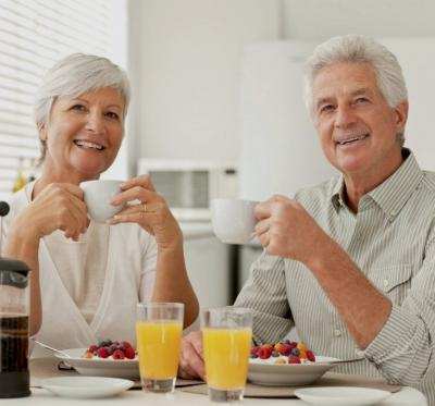 An active older woman and man at the breakfast table and smile.