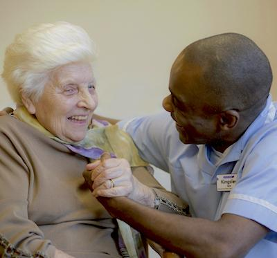 An older woman smiles as she interacts with her carer.