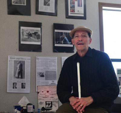 Man who is living with sight loss poses with some of his photographic works in the background.